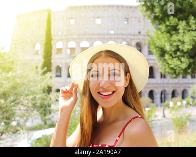 Portrait of smiling beautiful tourist girl in Rome with Colosseum on the background. Summer holidays in Italy. - Stock Photo
