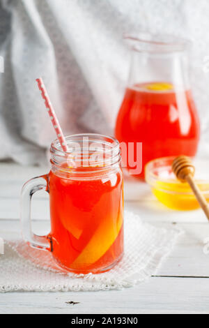Strawberry lemonade with honey in mason jar and in jug on white wooden table - Stock Photo