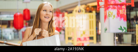 BANNER, LONG FORMAT Woman hold shopping bag against the background of Chinese red lanterns for the Chinese New Year. Big sale in honor of the New Year - Stock Photo