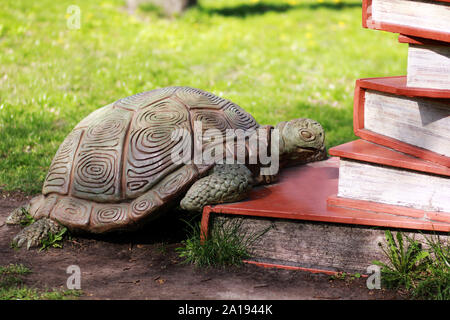 Bucha, Ukraine, 1 May 2017 - Sculpture of a turtle climbing on pile of books - Stock Photo