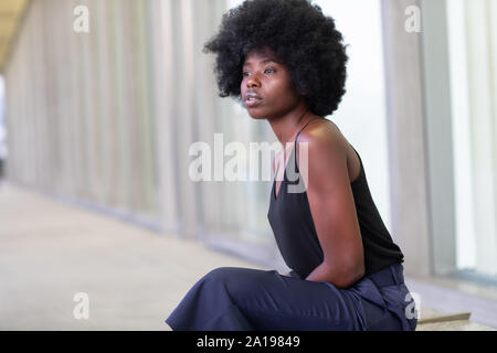 Pretty young African woman on city streets, sitting on the bench Stock Photo