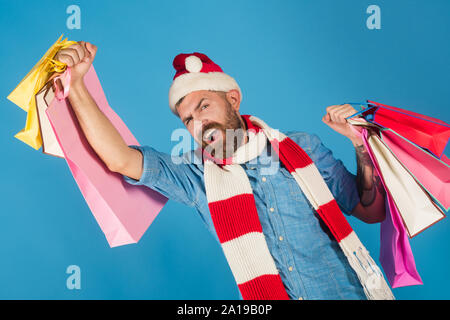 Christmas winter holidays celebration. Black friday sale concept. Man shopper smile in santa hat and scarf. New year, xmas presents. Hipster hold shop