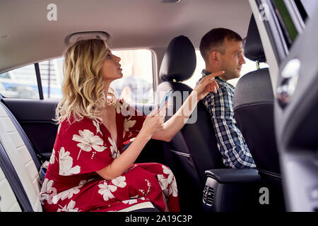 Photo of blonde woman looking at camera sitting in back seat of car during day - Stock Photo