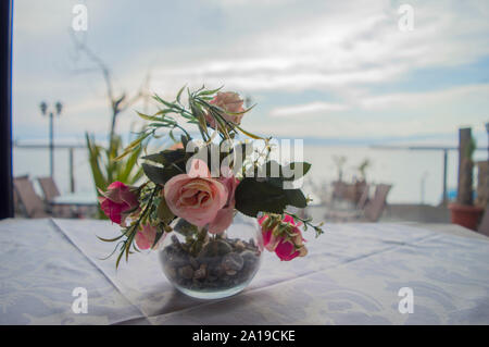 Bouquet of colorful flowers in a glass vase on a table at a restaurant. - Stock Photo