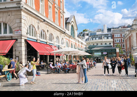 Tourists enjoying the summer weather at Covent Garden Piazza in London's West End, London, England, UK - Stock Photo