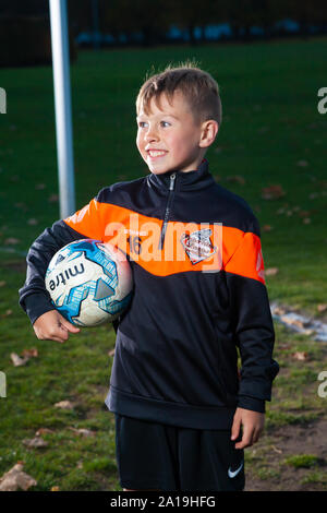 An eight year old boy wearing a soccer strip and holding a football under his arm. - Stock Photo