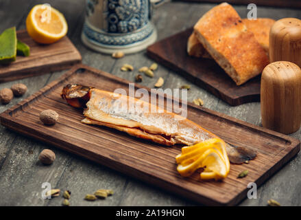 Fish on the wooden board with lemon - Stock Photo