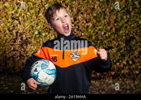 An eight year old boy wearing a football strip and holding a football under his arm with the other hand in a fist. - Stock Photo