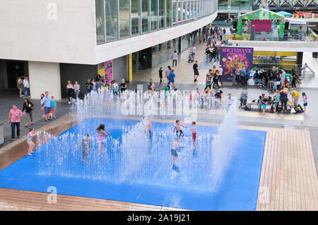 Children having fun playing in the water jet fountains in the Appearing Rooms installation by Danish artist Jeppe Hein, Southbank Centre, London, UK - Stock Photo