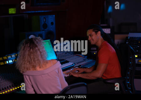 Male and female music producers working together in a sound studio - Stock Photo
