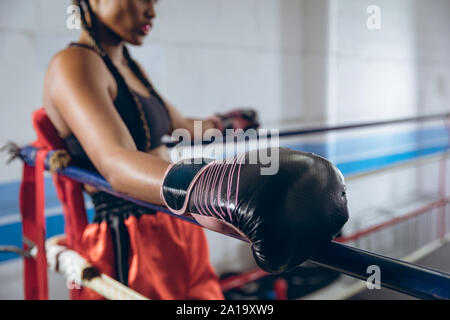 Female boxer resting in the corner of the boxing ring at boxing club - Stock Photo