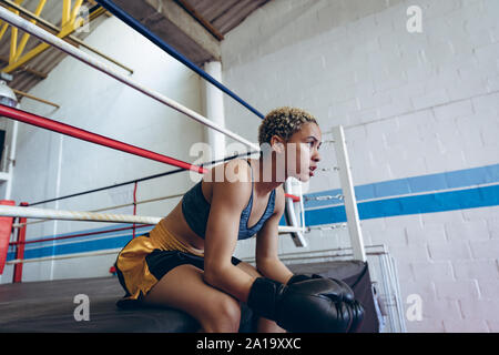 Female boxer resting in boxing club - Stock Photo