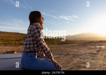 Young woman sitting on a pick-up truck during a stop off on a road trip