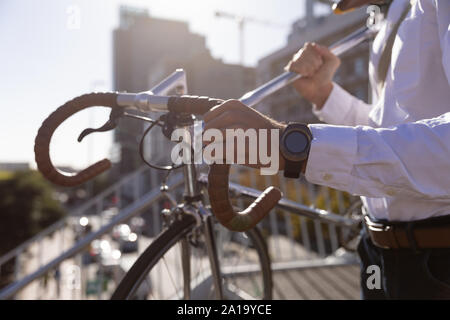 Young professional man carrying a bike