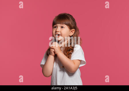 Close-up portrait of a little brunette girl dressed in a white t-shirt posing against a pink studio background. Sincere emotions concept. - Stock Photo