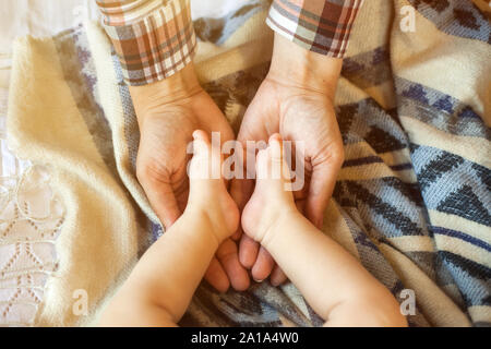 Cute little baby's legs in mother's hands close up in bed at home. Family, maternity and childhood concept. - Stock Photo