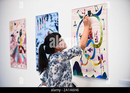 London, UK.  25 September 2019.  Artist Ming Lu poses with some of her ornate tapestries at the preview of START, a contemporary art fair comprising eclectic works from a variety of international emerging artists.  The fair takes place at the Saatchi Gallery in Chelsea 26 to 29 September 2019. Credit: Stephen Chung / Alamy Live News - Stock Photo