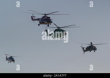 29 AUGUST 2019 MOSCOW, RUSSIA: Four helicopters flying in the gray sky. Mid shot - Stock Photo
