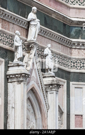 East entrance to Giotto's Campanile tower, Florence, Italy. 'Two Prophets and the Redeemer' on top of the gable above the entrance door, are both attr - Stock Photo