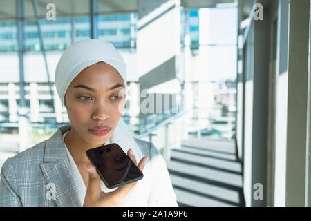 Businesswoman in hijab talking on mobile phone in corridor at modern office - Stock Photo