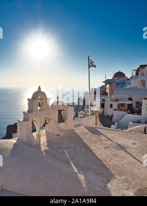 Picturesque view of belfry with hanging bells Greek flag and domed church with blue sea on background in Oia Santorini Greece on sunny day
