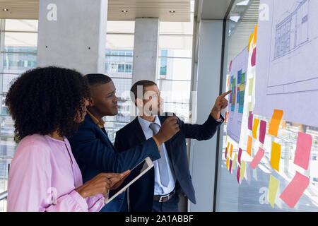 Three young business people in discussion in a modern office Stock Photo