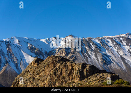 Scene view of mountain climbers reaching mountain peak against snow-capped Andes mountains in Patagonia, Esquel, Argentina