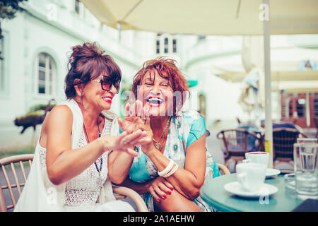 Image of a two happy senior women friends sitting in cafe talking with each other drinking coffee, laughing and pointing fingers to someone. - Stock Photo