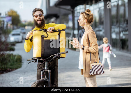 Male courier delivering food with a bicycle to a young businesswoman, getting some packages from a thermal bag outdoors - Stock Photo