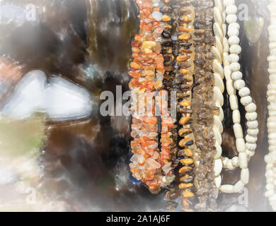 watercolor illustration: Hanging jewellery necklaces with coloured semi-precious stones, coloured stones and small white ivory pieces and amber. - Stock Photo