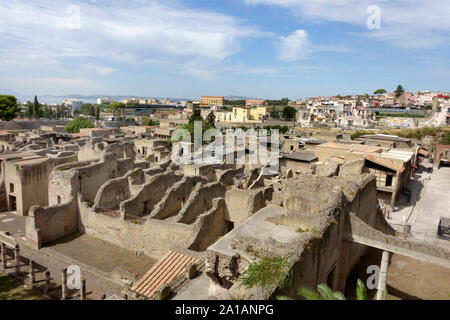 The ancient city of Herculaneum, Italy. With at the background the modern city and the coastline with the harbour and the Gulf of Naples - Stock Photo