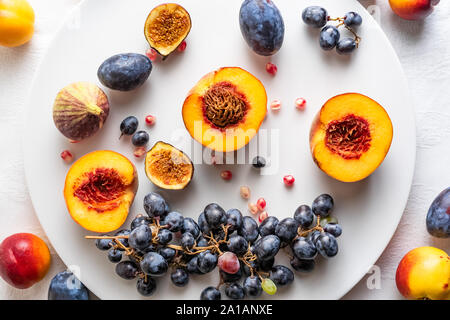 Halved peaches, nectarines, grapes, figs on white plate on white tablecloth. Top view, horizontal orientation - Stock Photo