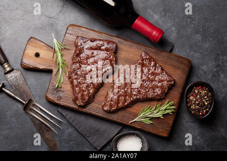 Grilled beef steak on wooden board and red wine. Top view flat lay