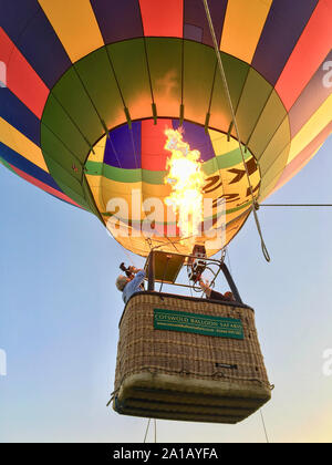 Hot-air balloon lifting off in field near Braunton, Devon, England, United Kingdom - Stock Photo