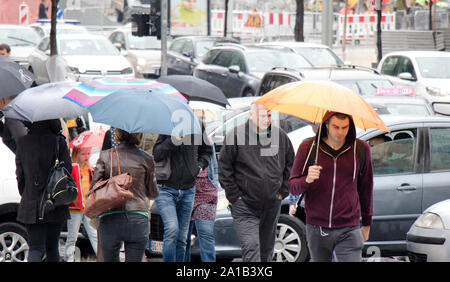Belgrade, Serbia- September 24, 2018: People under umbrellas crossing the street in rush hour with many cars in traffic jam on a rainy day in the city - Stock Photo