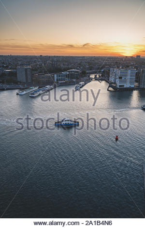 Ferry in Amsterdam crossing IJ in the evening - Stock Photo