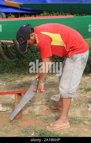 Laotien sciant une planche de bois pour la rénovation d'une barque. Vieng Vang. Laos. / Lao sawing a wooden board for the renovation of his boat. - Stock Photo
