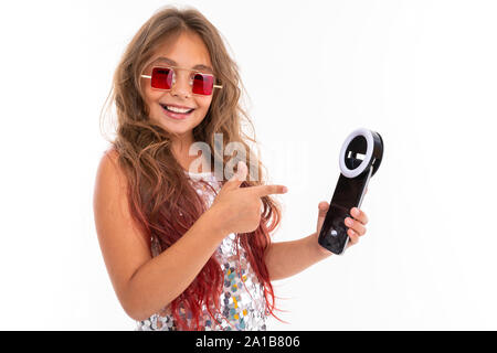Smiling girl in square red sunglasses holding black cellphone light-emitting-diode for selfie and pointing at it isolated - Stock Photo