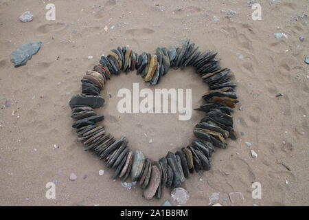 Heart shape made from slate on sandy beach - love concept - from above - nature inspired - love nature - Stock Photo