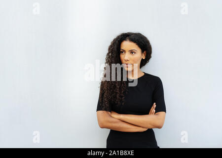 Thoughtful young woman standing staring to the side with folded arms watching intently, with copy space - Stock Photo