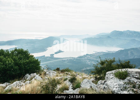 Stone mountains in the foreground and plants and in the background view from the top of the mountain to the Kotor Bay in Montenegro. Natural mountain landscape and the sea. - Stock Photo