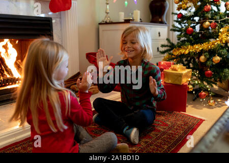Brother and sister at home at Christmas time - Stock Photo