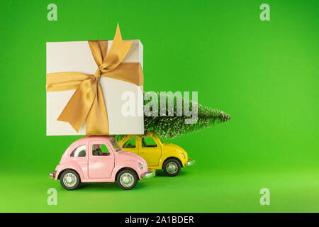 Vilnius, Lithuania - September 09, 2019: Little retro toy model cars with present gift box and small Christmas tree on green background - Stock Photo