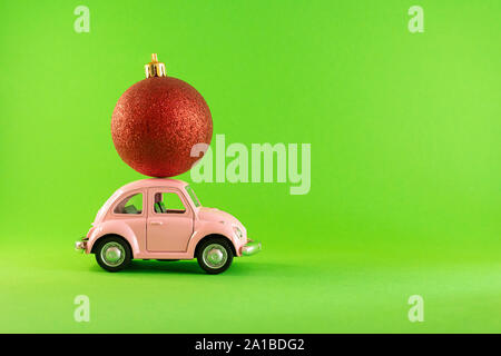 Vilnius, Lithuania - September 09, 2019: Pink retro toy model car with small red Christmas tree decoration bauble on green background - Stock Photo