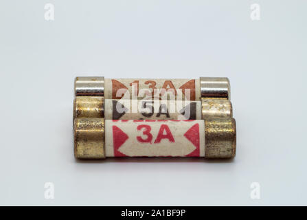 UK plug fuses 3 Amps 5 Amps and 13 Amps on a white background - Stock Photo