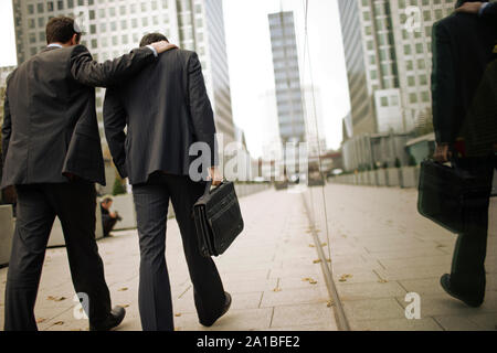 Two businessmen walking home together through city streets. - Stock Photo