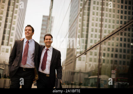 Businessman puts his arm around his friend's shoulder as they walk along a city street. - Stock Photo