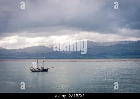 The Menai Strait at Beaumaris.  A sailing ship manoeuvres against a backdrops of cloud topped hills. - Stock Photo