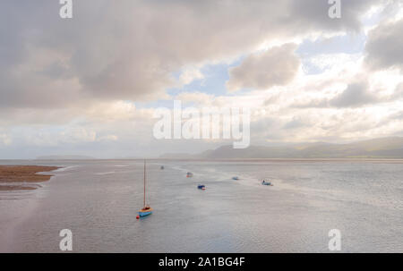 The Menai Strait at Beaumaris.  Boats are moored near the land with a yacht in the foreground.  A heavy cloud is above. - Stock Photo