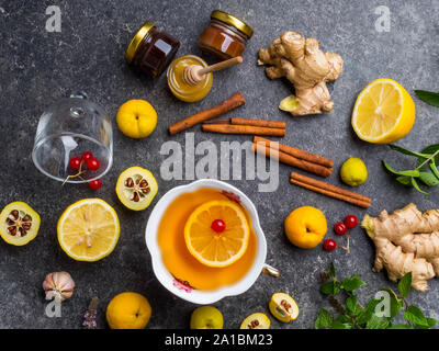 backgroundof cup of ginger tea with lemon, cranberry, different honey in jars, cydonia, cinnamon sticks on concrete background - Stock Photo